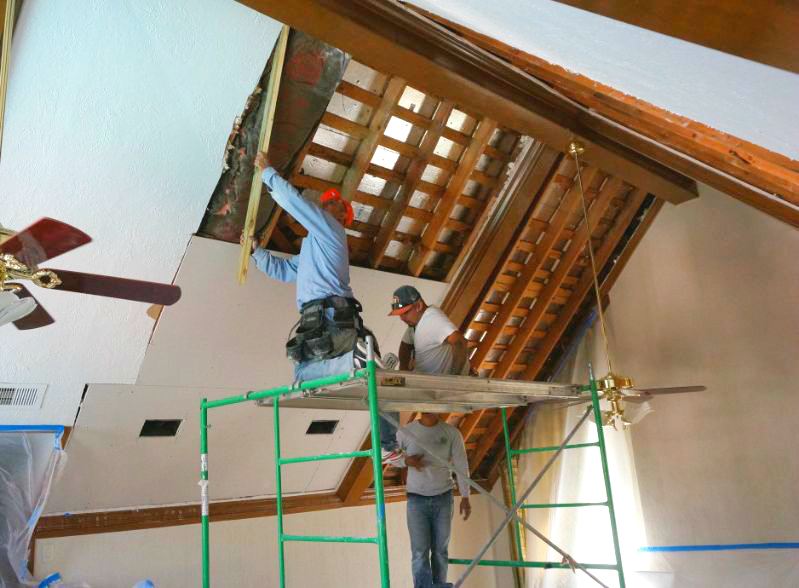 Three men installing residential drywall in house