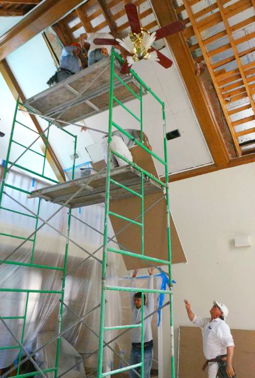 Five men installing residential drywall in house. Two men are on top of scaffold. One man is on level below top level of scaffold and he is picking up drywall from a man on ground level.