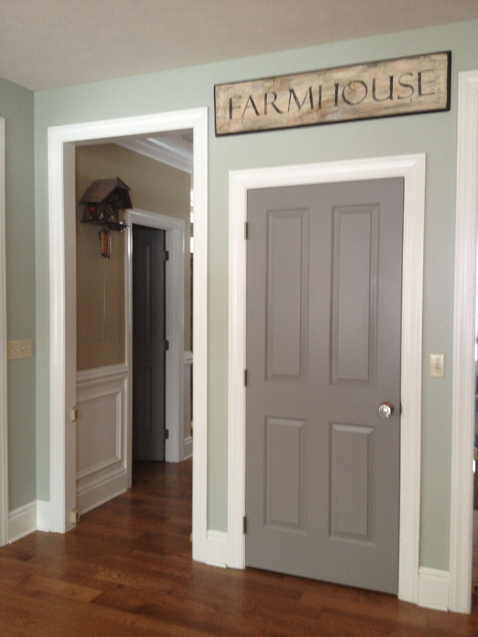 Residential interior walls painted new color. There is a door with a sign that says Farmhouse above it and also a wall clock in the hallway.