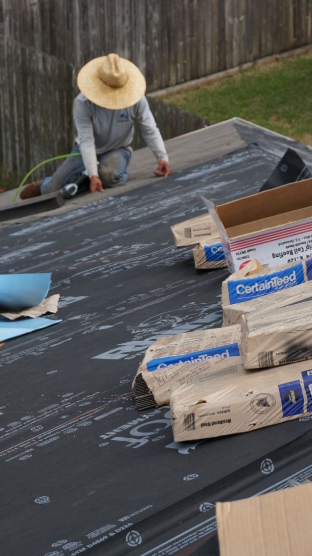Man on roof putting covering on roof for residential shingle roof installation and repairs