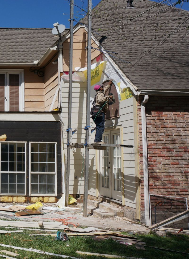 Man on scaffold working on residential siding of house
