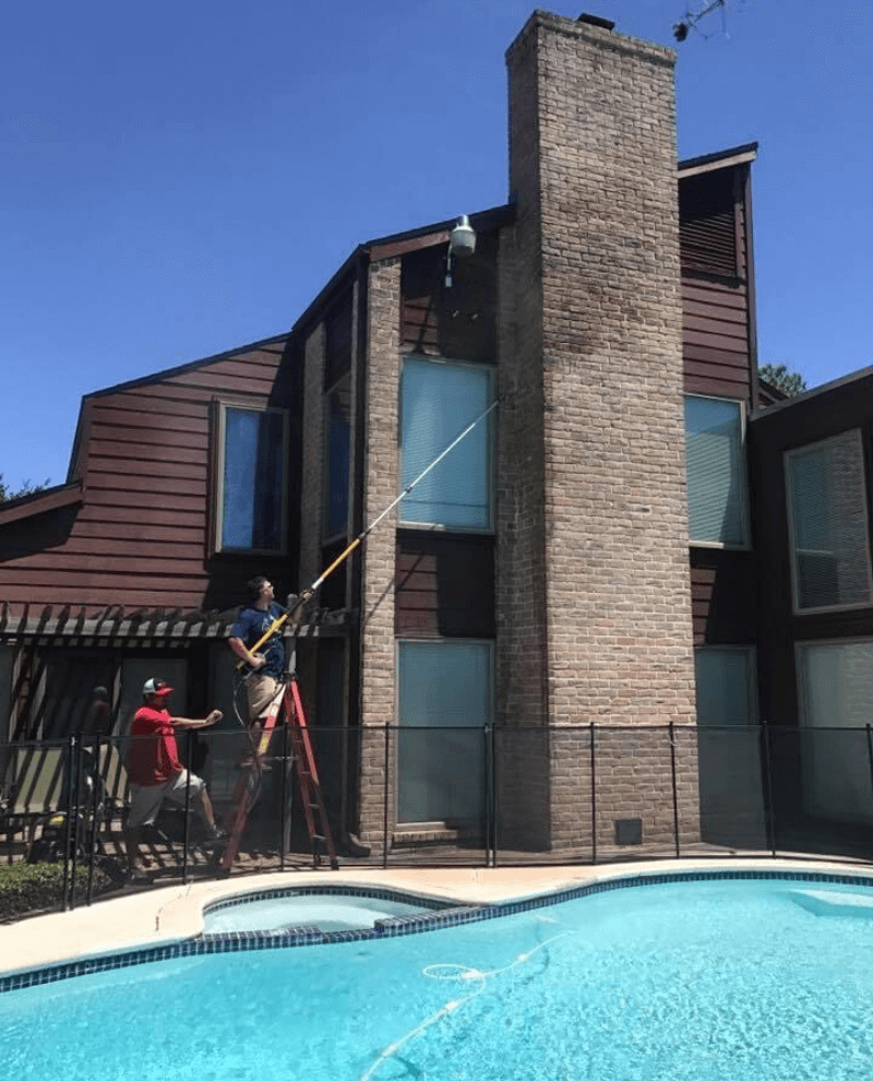 Man wearing red shirt, blue hat, and black boots powerwashing driveway of house. There are bushes lining the front of the house and a ladder next to the man.